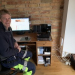 Bild på Christian när han sitter vid datorn. Han vänder blick mot kameran och ler. Golvet som syns är av trä och väggen bakom datorn är av tegel. Hans skrivbord som datorn står på är av trä. Han är iklädd arbetskläder.